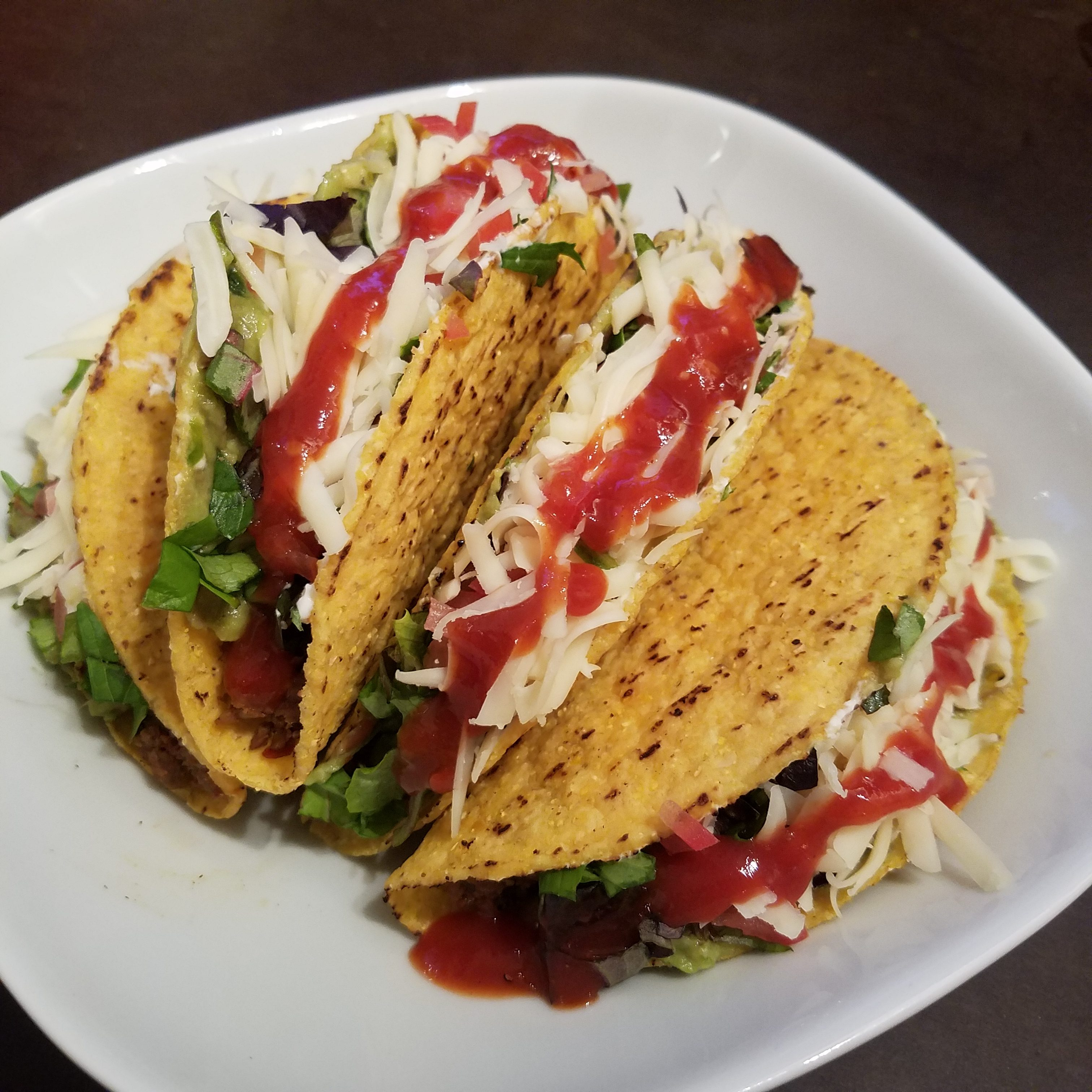 Loaded tacos with Lettuce Tomatoes, cheese, sour cream, guacamole, taco sauce